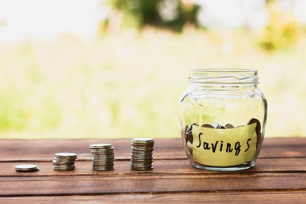 Vaso con risparmio e pila di monete sul tavolo