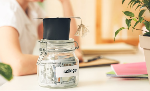 Jar with savings for education and graduation cap on table of girl at home