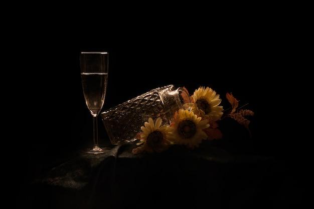 ひまわりと黒い背景で隔離のテーブルの上のシャンパングラスと瓶