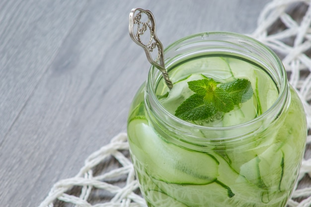 Jar with tasty cucumber lemonade on wooden table