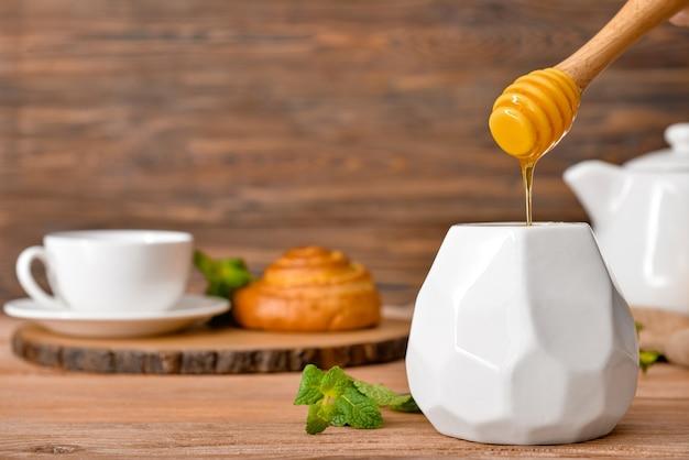 木製のテーブルにおいしい蜂蜜と瓶