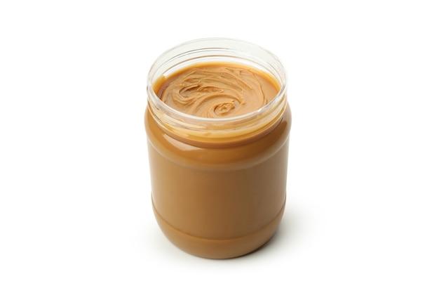 Банка с вкусным арахисовым маслом на белом фоне