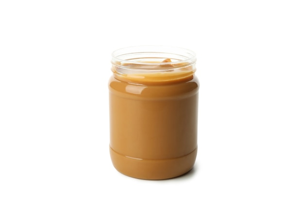Jar with tasty peanut butter isolated on white background
