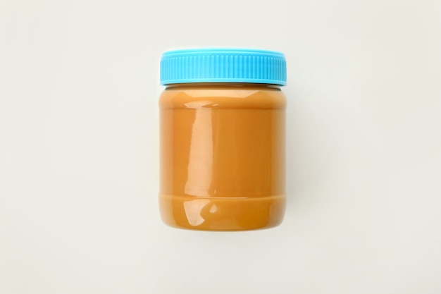 Jar with tasty peanut butter isolated
