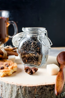 Jar with tea, homemade cookies and  spices for tea on dark   background,