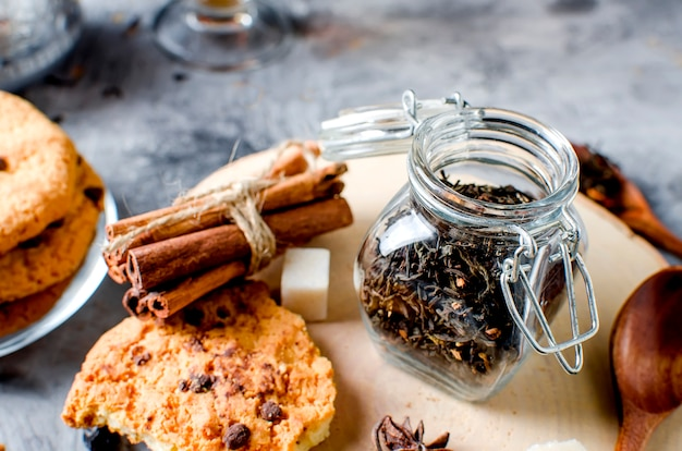 Jar with tea, homemade cookies and  spices for tea on dark  background