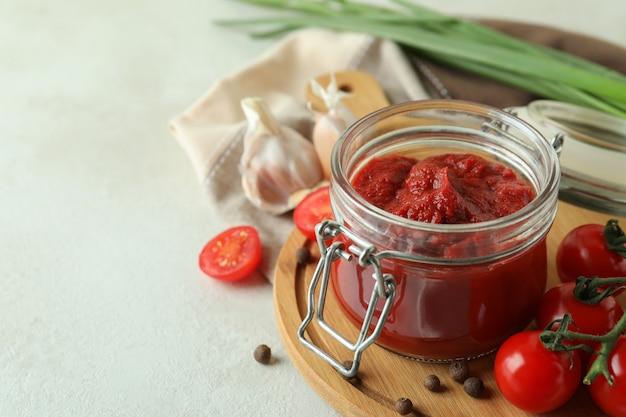 白い織り目加工のテーブルにトマトペーストと材料の瓶