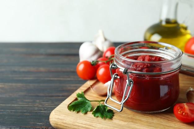 재료와 나무 테이블에 토마토 페이스트와 항아리