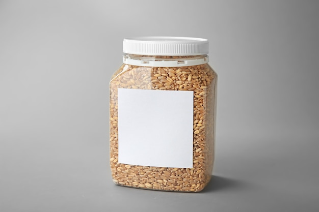 Jar with wheat grass seeds on grey