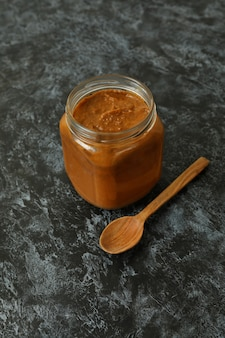 Jar with zucchini caviar and wooden spoon on black smokey