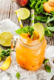 夏の飲み物、カクテル。ビーガンフード桃のスムージー、ジュース、レモネード。石灰が入った石工のjarに