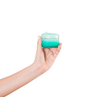 分離されたローションのクリームボトルを持っている女性の手。女の子はjar化粧品を与える