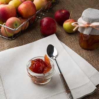 Jars of apple jam with fresh fruits