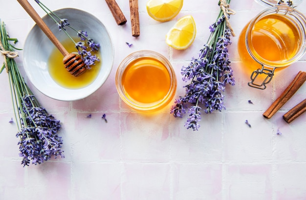 Jars and bowl with honey and fresh lavender flowers on a pink tile background