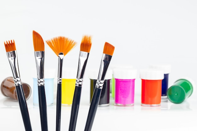 Jars of colorful paints with different brushes for painting
