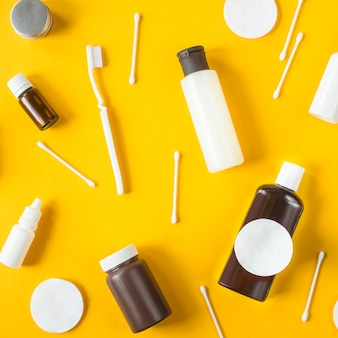 Jars and containers with cosmetics, cotton buds and disks and toothbrush scattered