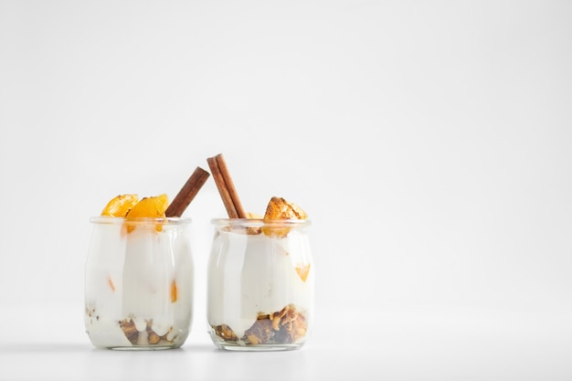 Jars of greek yogurt with granola, cinnamon and canned apricots