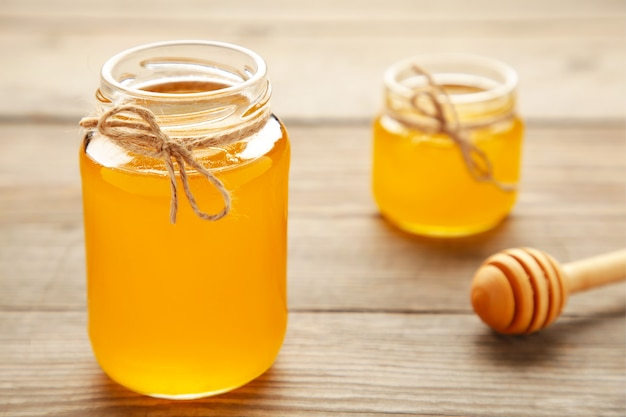 Jars of honey on wooden table. top view