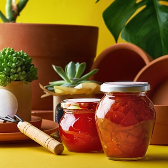 Jars of jam from the home garden. potted plants and clay pots in assortment for gardening