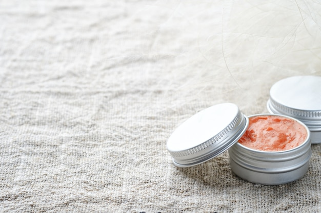 Jars of natural cosmetic on a linen napkin