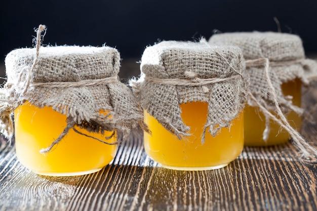 ガラス製の蜂蜜の瓶は蓋と亜麻布で覆われ、新鮮な蜂の蜂蜜はガラスの瓶に詰められています