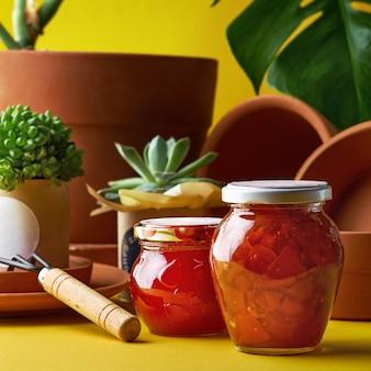 家の庭からのジャムの瓶。園芸用の品揃えの鉢植えと土鍋