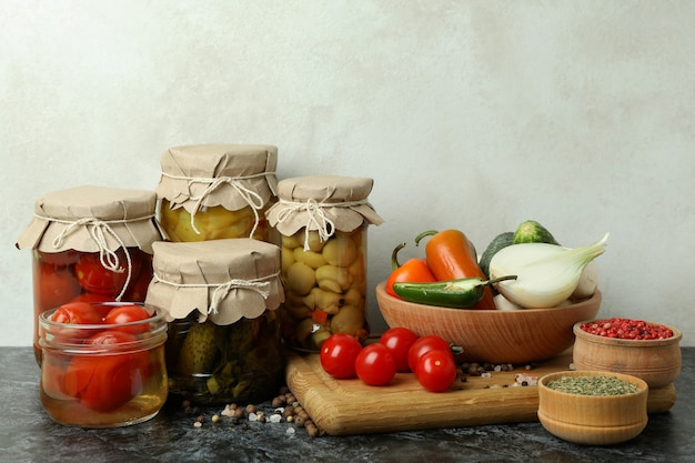 Банки маринованных овощей и ингредиентов на черном дымчатом столе