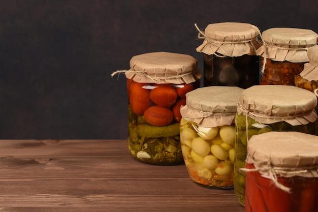 漬物の瓶。マリネした食品。コピースペースを持つ木製の背景に缶詰の野菜の瓶。
