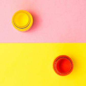 黄色とピンクの表面に赤と黄色のペンキの瓶