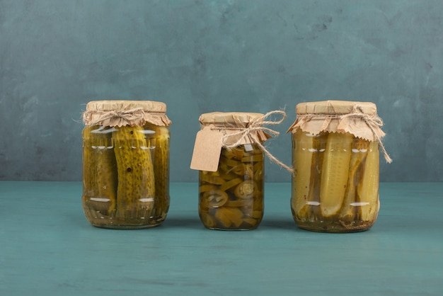 Jars of pickled cucumbers and jalapenos on blue table.