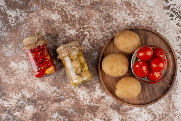 Jars of pickled peppers and mushrooms and plate of boiled potatoes, pickled tomatoes on marble surface.