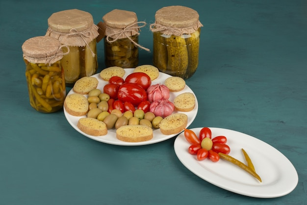 Jars of pickled vegetables, boiled potatoes and plate of marinated vegetables on blue table.