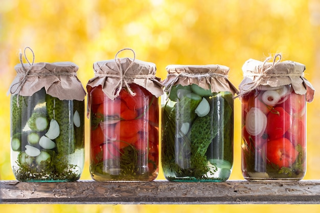 Jars of pickled vegetables: cucumbers, tomatoes on a wooden shel