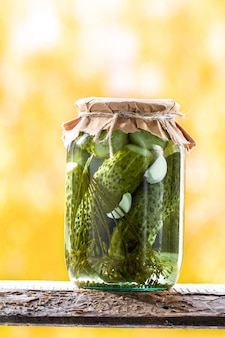 Jars of pickled vegetables: cucumbers on a wooden shelf
