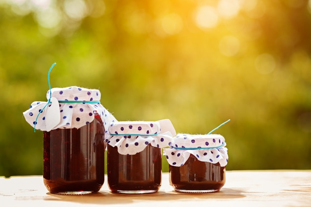 Jars with berries jam on green nature background.