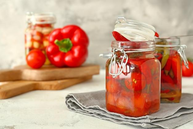 Банки с консервированными помидорами и перцем чили на столе