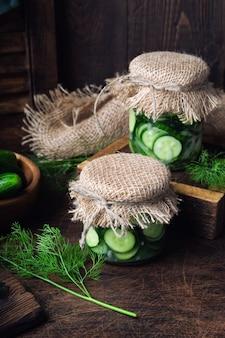 Банки с домашними солеными огурцами, нарезанными дольками с укропом и чесноком на деревенской деревянной поверхности. заготовка овощей на зиму.