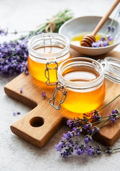 Jars with honey and fresh lavender flowers on a concrete background