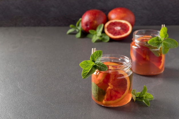 Jars with kombucha and bloody oranges on grey table