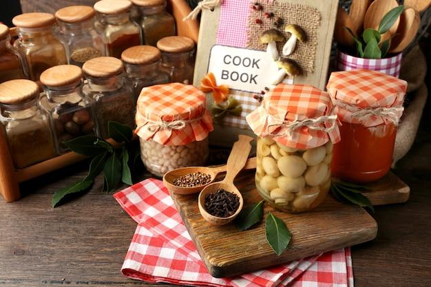 Банки с маринованными овощами и фасолью, специями, книга рецептов и кухонная утварь на деревянном фоне