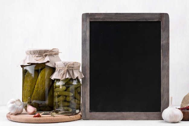 Jars with pickles and blackboard