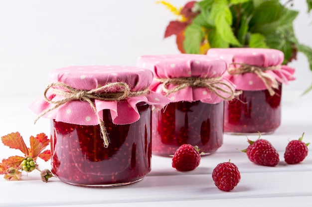 Jars with raspberry jam placed in rows and fresh raspberry on white wooden table