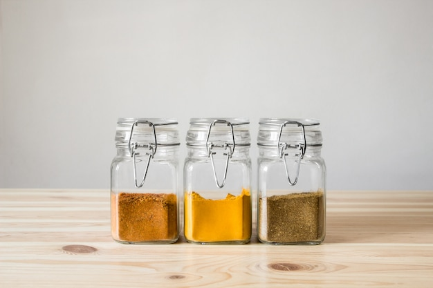 Jars with spices on light wood table