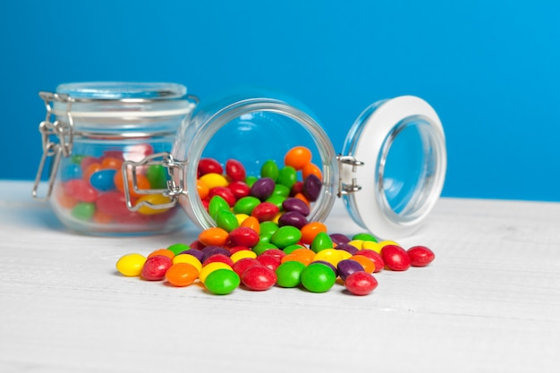 Jars with sweet candies on table
