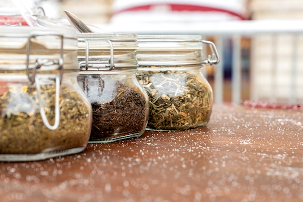 代替医療と自然食品の3種類のお茶が入った瓶がテーブルにあります。淹れるための乾燥した形のお茶は、ガラスの瓶に保管されます。ストリートマーケット。