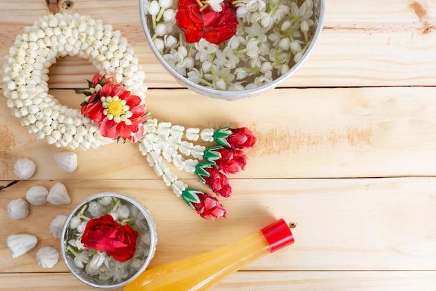 木材の背景にジャスミンと白いバラのガーランド。タイのソンクラン祭り。タイの伝統。