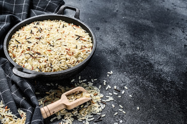 재스민, 브라운, 레드, 블랙 라이스. 혼합 쌀과 riceberry. 검정색 배경. 평면도. 공간을 복사하십시오.