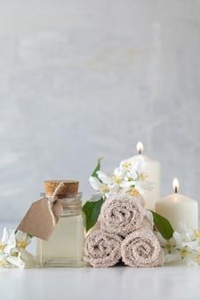 Эфирное масло жасмина, свечи и полотенца, цветы