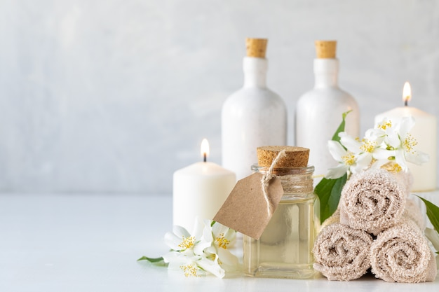 Jasmine essential oil, candles and towels, flowers on a white background. spa and wellness concept. copy space.