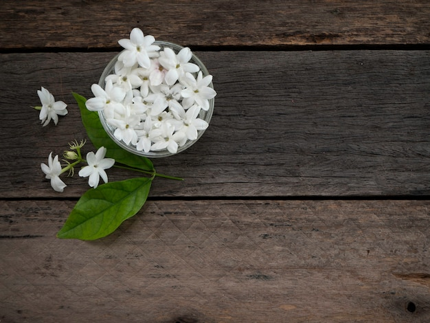 Jasmine floating in clear glass  on wooden background.